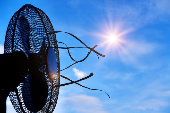 a fan blowing toward a blue sky. The sun is shining directly above