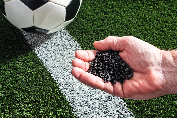 a human hand holds rubber granules over soccer turf with a soccer ball present