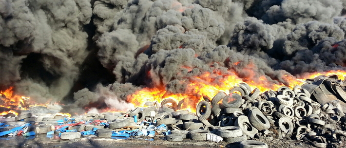 a pile of tires spewing out black smoke and flames